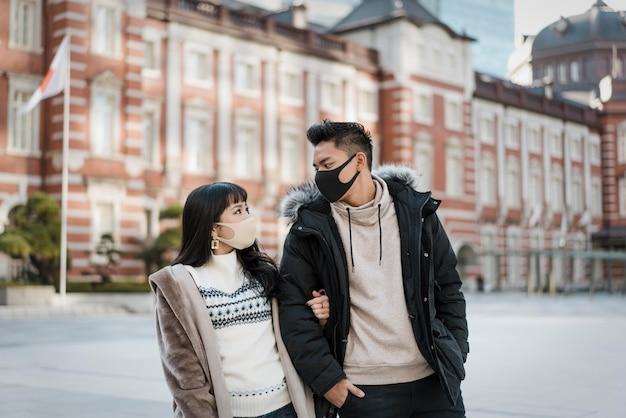 Couple à l'extérieur avec des masques médicaux