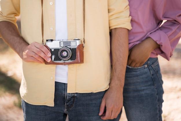 Couple à l'extérieur posant avec caméra