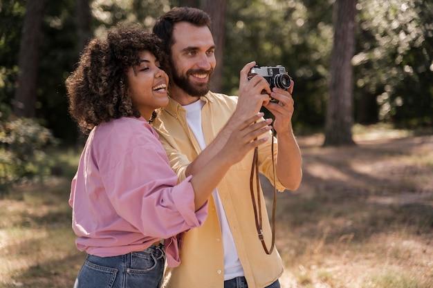 Couple à l'extérieur, prendre des photos avec appareil photo