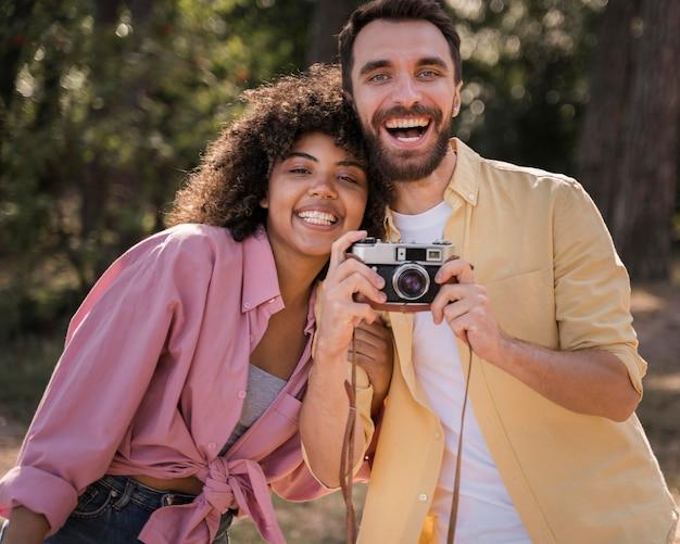 Couple à l'extérieur tenant et prendre des photos avec appareil photo
