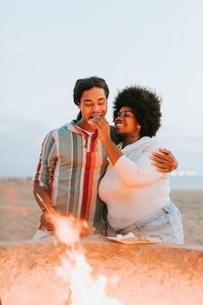 Couple, faire griller des guimauves sur un feu de joie