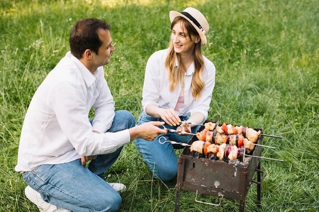 Couple faisant un barbecue dans la nature