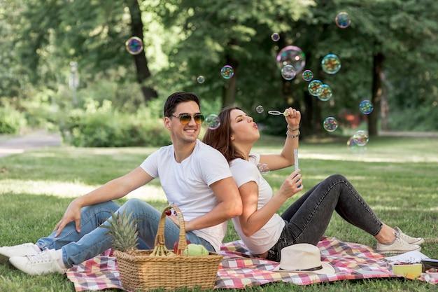 Couple faisant des bulles assis dos à dos