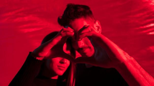 Couple faisant le coeur des mains