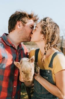 Couple faisant du bénévolat dans un sanctuaire pour cochons