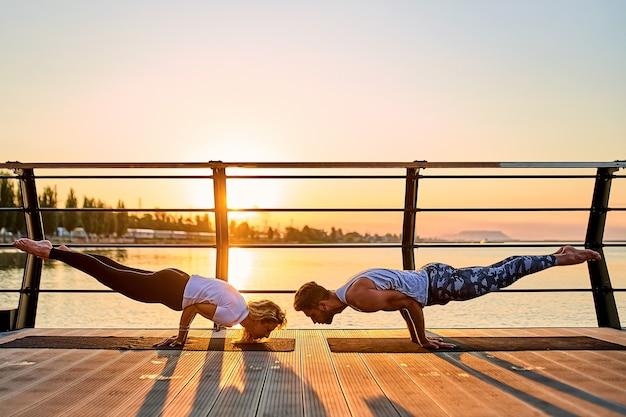 Couple faisant du yoga ensemble sur la nature à l'extérieur des exercices matinaux au lever du soleil