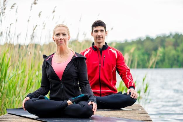 Couple faisant du yoga sur la jetée au lac