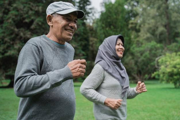 Couple faisant de l'exercice en courant dans le jardin