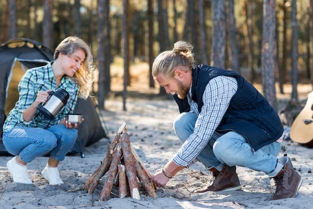Couple faisant un feu de camp dans la nature