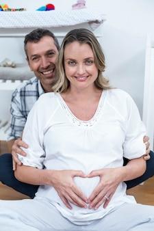 Couple faisant une forme de coeur sur le ventre de femme enceinte avec leurs mains