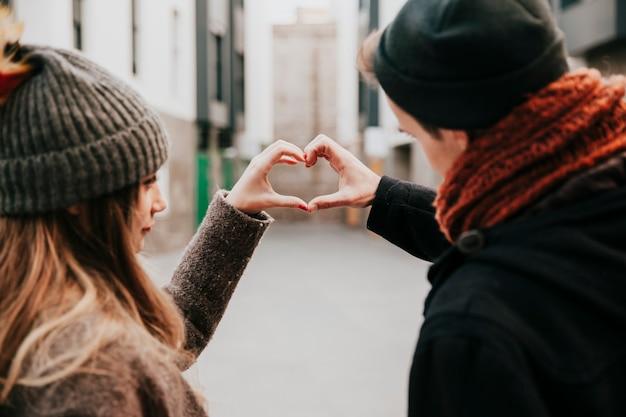 Couple faisant le geste du cœur de la main