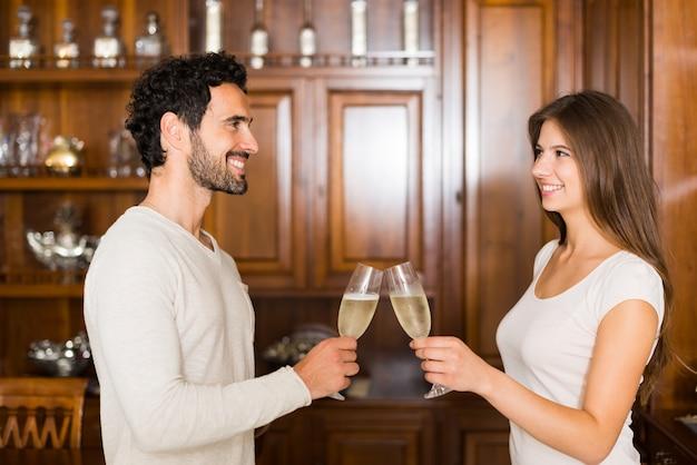 Couple faisant griller du champagne dans leur appartement