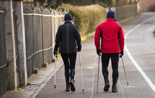 Couple faisant de la marche nordique en hiver