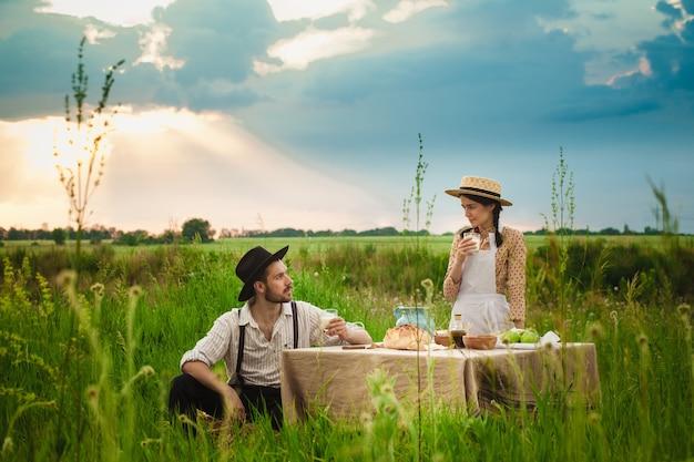 Couple faisant un pique-nique dans le pré