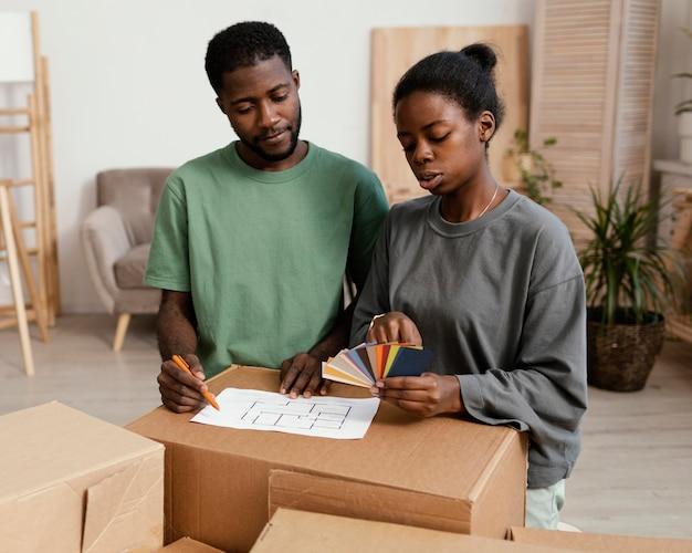 Couple faisant un plan pour redécorer la maison ensemble