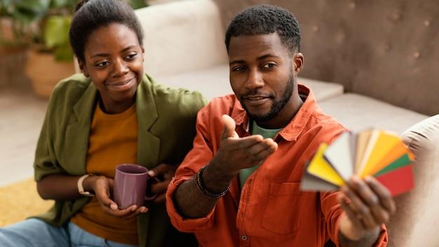Couple faisant des plans ensemble pour rénover la maison à l'aide de la palette de couleurs