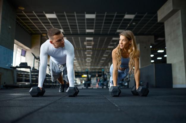 Couple faisant des pompes avec des haltères en salle de sport