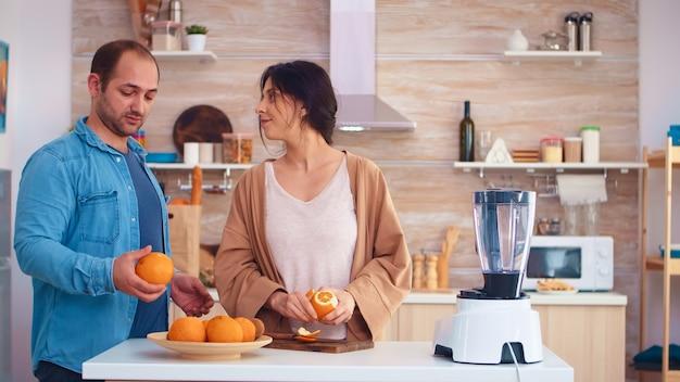 Couple faisant un smoothie dans la cuisine. femme qui pèle d'orange tout en souriant à son mari. joyeuse famille faisant ensemble du jus de fruits frais et nutritif biologique sain pour le petit-déjeuner à partir de fruits frais tout en