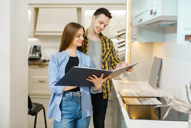 Couple de famille choisissant la garniture de cuisine dans la salle d'exposition de magasin de meubles.