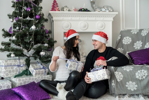 Couple de famille avec des coffrets cadeaux assis près de la cheminée