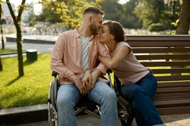 Couple de famille avec fauteuil roulant assis sur un banc dans le parc. personnes paralysées et handicaps, prise en charge d'un homme handicapé. mari et femme surmontent les difficultés ensemble, relations chaleureuses