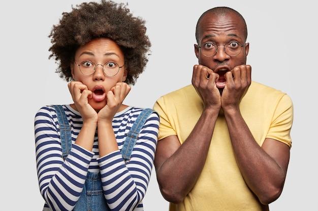 Un couple de famille formidable garde les mains sous le menton, regarde avec des expressions effrayées, effrayé par un terrible accident