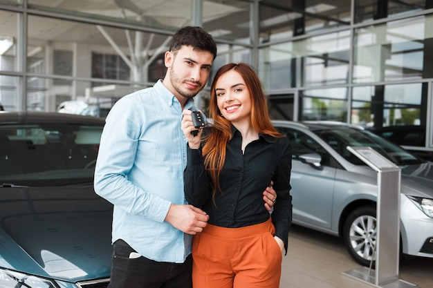 Couple de famille heureux avec une clé de leur nouvelle voiture