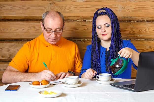 Un couple de famille un homme à lunettes et une femme avec des tresses afro bleues à la table une femme verse du thé un homme écrit des informations