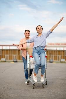 Un couple de famille monte en chariot sur un parking de supermarché