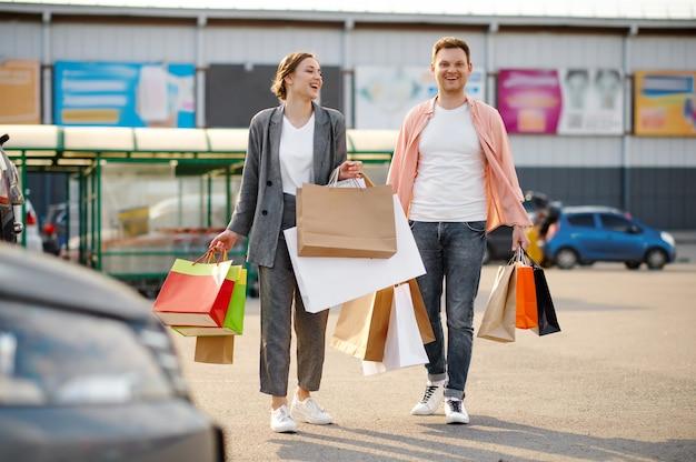Couple de famille avec des sacs sur le parking du supermarché