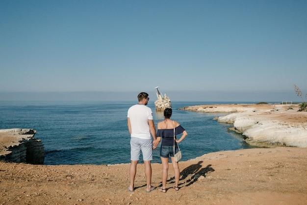 Couple famille voyageant ensemble près de l'océan à chypre. concept de mode de vie homme et femme vacances d'été en plein air. beau paysage naturel sur la vue latérale en arrière-plan