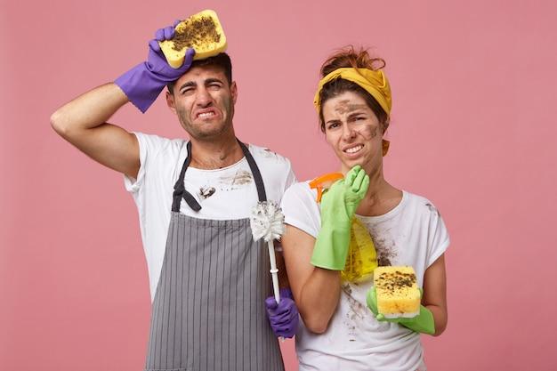 Couple fatigué et désordonné nettoyant la maison