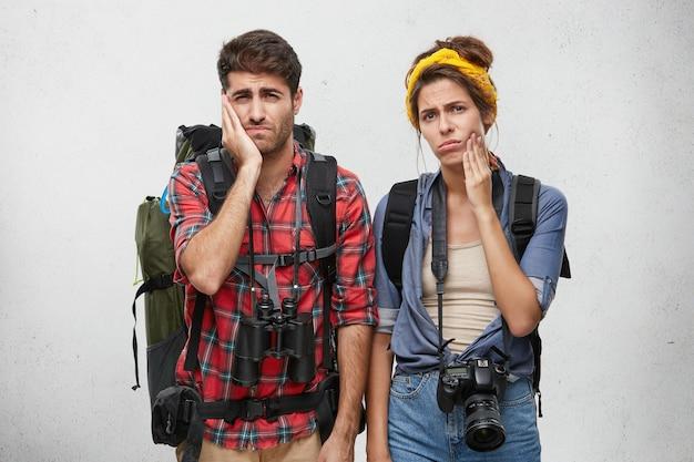 Couple fatigué habillé avec désinvolture posant