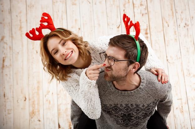 Couple en fausses cornes de cerf posant s'amuser sur le mur en bois