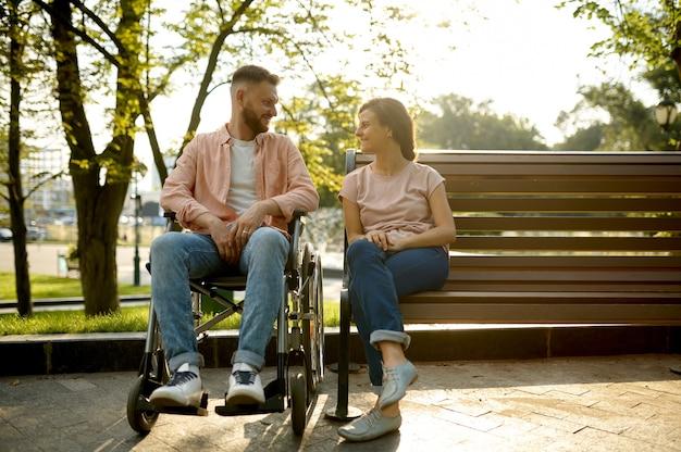 Couple avec fauteuil roulant assis sur un banc dans le parc