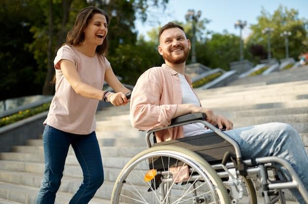 Couple avec fauteuil roulant monte les escaliers dans le parc
