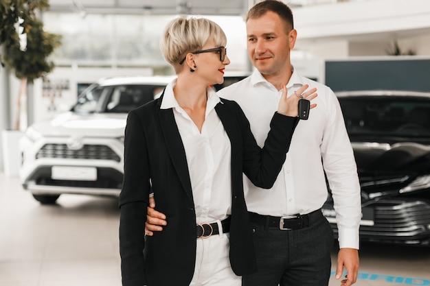 Couple femme et mari concessionnaire automobile souriant joyeusement. femme tenant une clé.