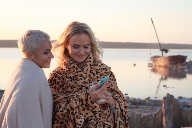 Couple de femmes adultes homosexuelles utilisent un smartphone sur la plage