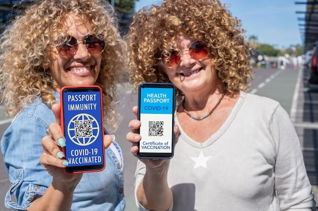 Couple de femmes bouclées et blondes prêtes à voyager montrant une certification de santé numérique pour les personnes vaccinées contre le coronavirus