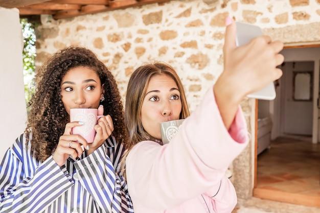 Couple de femmes lgbt faisant un autoportrait en pyjama en maison de vacances