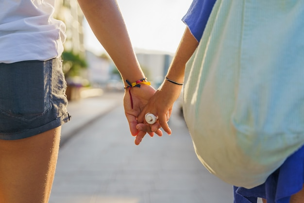 Couple de femmes méconnaissables se tenant la main