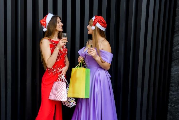 Couple de femmes en robes élégantes célébrant et portant un toast à la fête du nouvel an