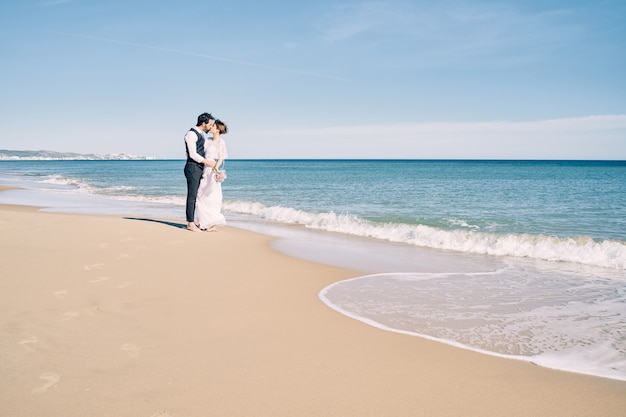 Couple fiancé s'embrassant sur la plage en robes de mariée