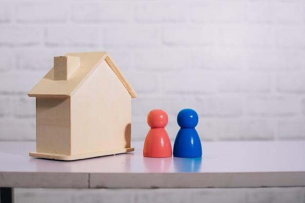 Couple de figurines en bois debout dans un modèle de maison