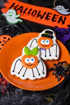 Un couple (fille et garçon) d'araignées drôles et amusantes peintes sur du pain d'épice au miel. nourriture d'halloween.