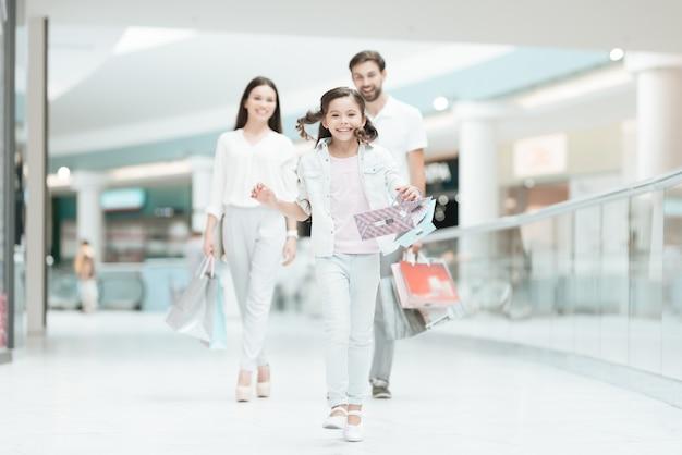 Couple avec fille marche dans un centre commercial.