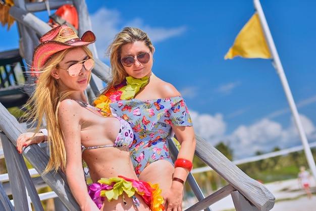 Couple de filles blondes sexy posant pour une prise de vue sur la plage