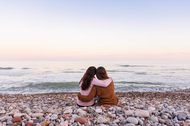 Couple de filles lesbiennes assis sur la plage en regardant et en appréciant un beau coucher de soleil ensemble