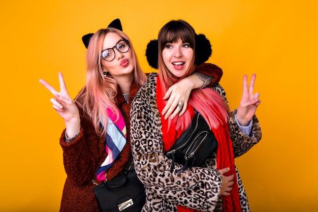 Couple de filles de soeur de meilleurs amis hipster assez drôles faisant selfie au mur jaune, montrant la langue et souriant, portant des manteaux de fourrure imprimés printaniers à la mode, des écharpes, un sac banane et des lunettes transparentes.