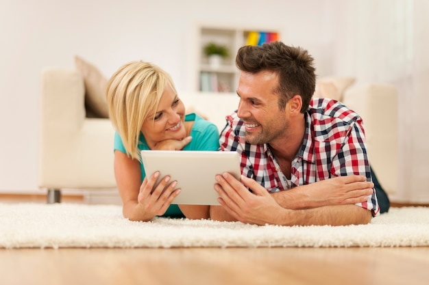 Couple de flirt à l'aide de tablette numérique sur tapis dans la salle de séjour
